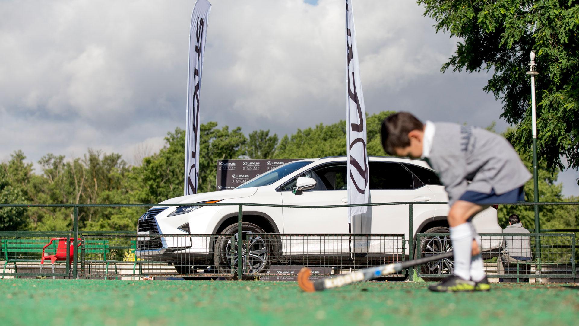 Imagen exterior del Lexus RX 450h y un niño empuñando un stick de hockey