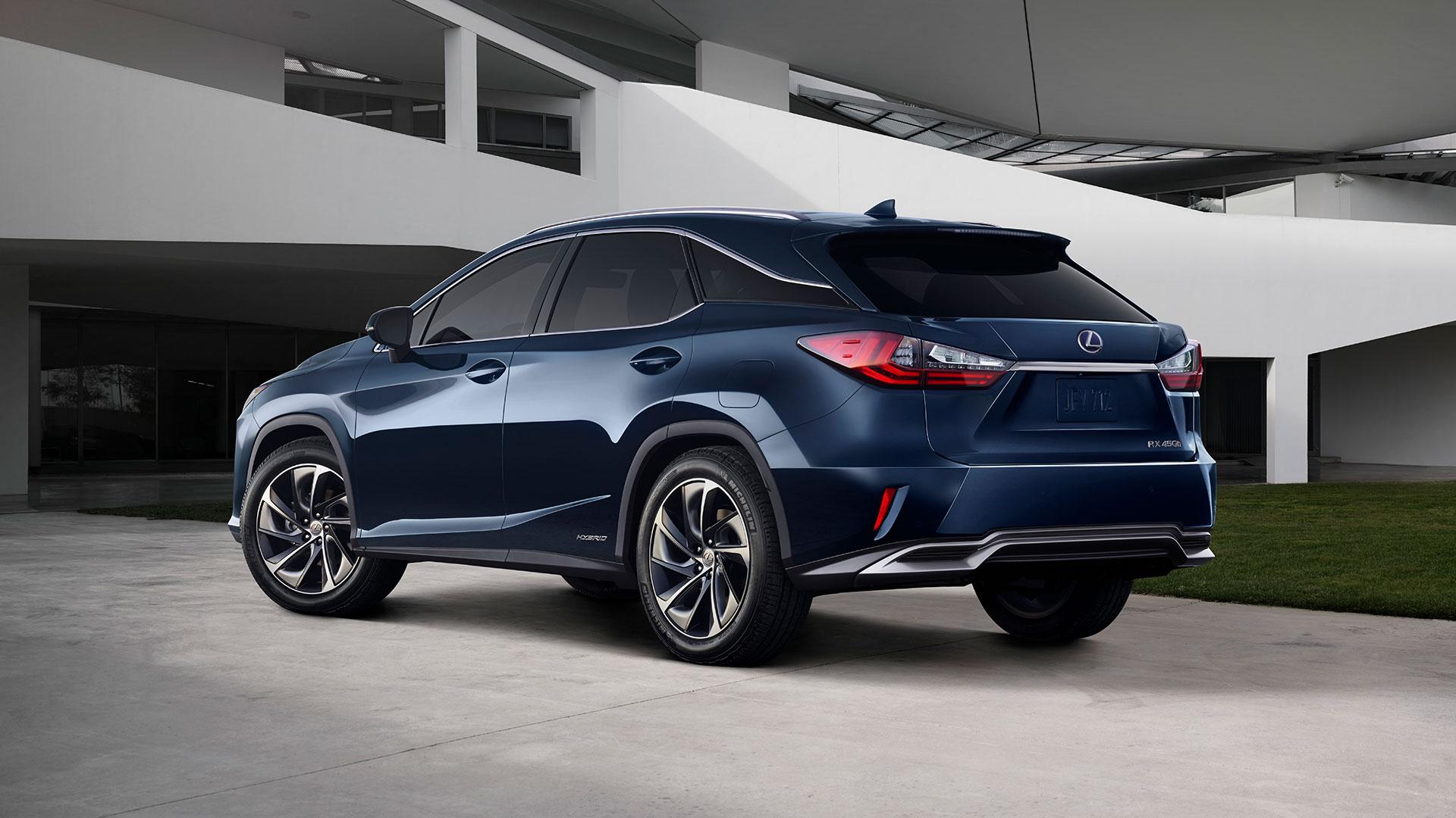 Blå Lexus RX selvladende hybrid SUV parkert foran et hvitt funkishus
