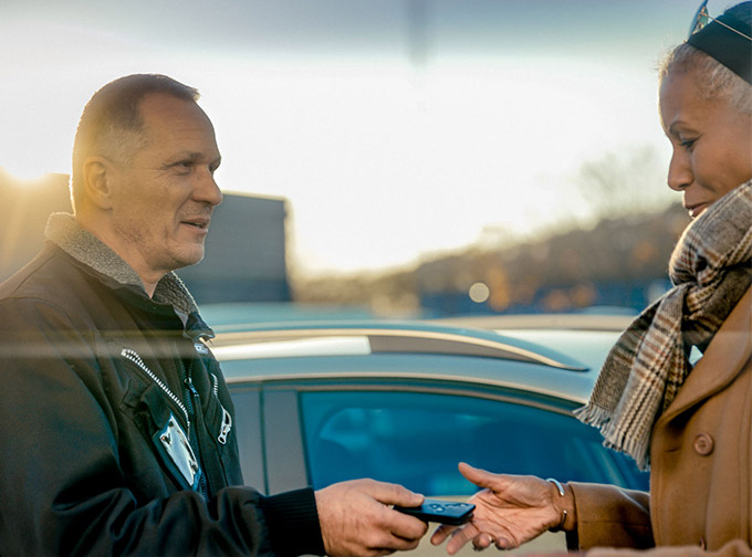 Bild på två personer Den ena lämnar en bilnyckel till den andre